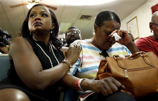 Phaedra Parks, left, comforts Desuirea Harris, the grandmother of Michael Brown, during a news conference Monday, Aug. 11, 2014, in Jennings, Mo. Michael Brown, 18, was shot and killed in a confrontation with police in the St. Louis suburb of Ferguson, Mo, on Saturday, Aug. 9, 2014. JEFF ROBERSON — AP Photo
